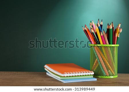 Books and metal holder of crayons on desk on green chalkboard background - stock photo