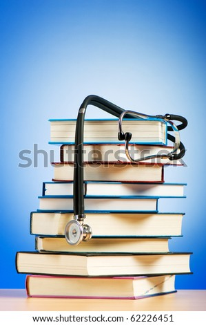 Books and stethoscope against the gradient background - stock photo