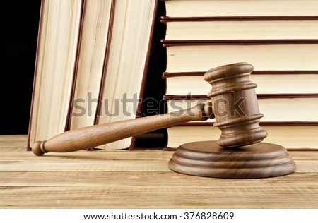 books and wooden gavel on black background - stock photo