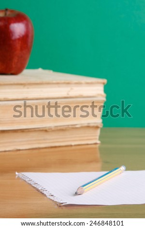Books, apple and a sheet of paper with a pencil on a desk - stock photo