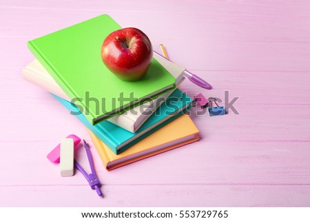 Books, apple and accessories on wooden background