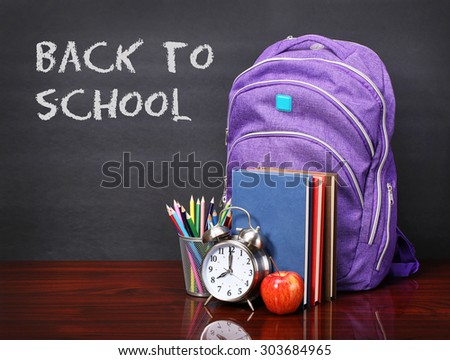 Books, apple, backpack, alarm clock and pencils on wood desk table. Text back to school on black board concept - stock photo