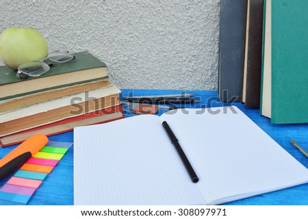 Books, apple, notebook,reading glasses, pencils on wood desk table and black board. Back to school concept.autumn