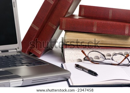 Books are strewd across a table, as somebody is doing research for an assignment paper. - stock photo