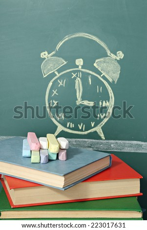 Books, chalk and chalk drawing of alarm clock and books - stock photo