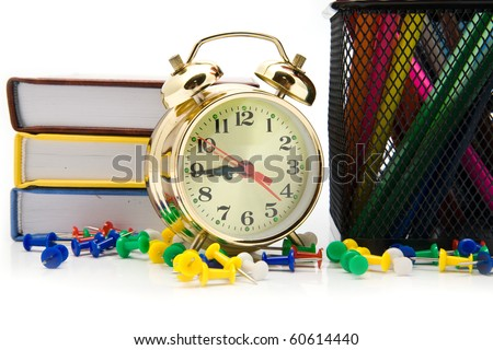 books, clock and pencils on a white background