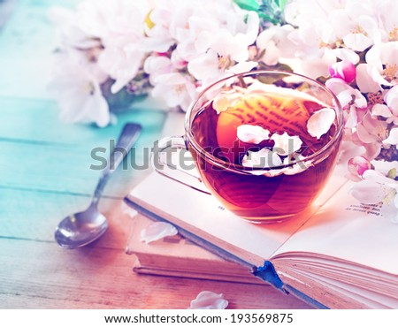 Books, flowers and cup of tea on wooden table - stock photo