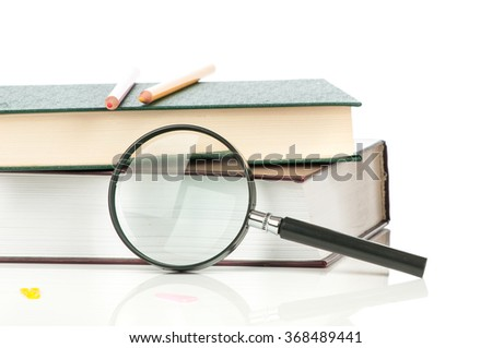 Books heap and magnifying glass isolated on white background. - stock photo