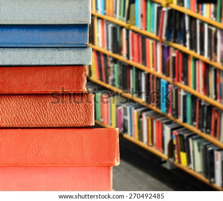 Books in pile, library shelves in background - stock photo