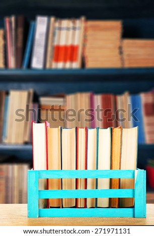 Books in wooden crate on bookshelves background - stock photo