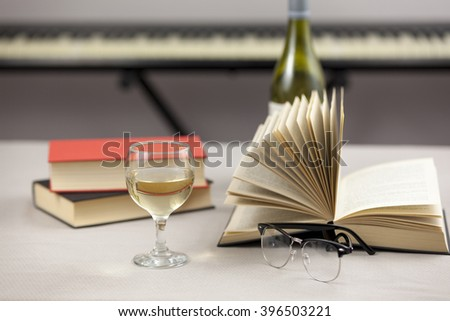 Books laying on a table with a half filled glass of wine and a pair of reading glasses - stock photo