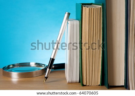 books, magnifier and ink pen on wood table - stock photo