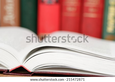 Books on a desk in library. - stock photo