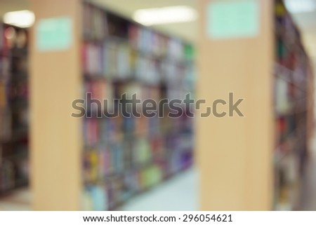 books on bookshelf in library, abstract blur defocused background - stock photo