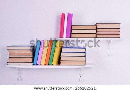 Books on shelves on white wall background - stock photo