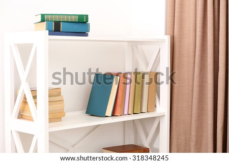 Books on shelves on white wall background - stock photo