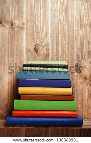 Books on the brown wooden shelf - stock photo
