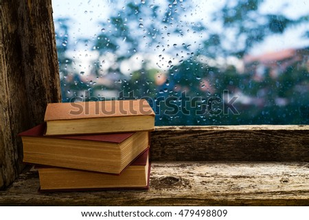 books on the windowsill of an old wooden window