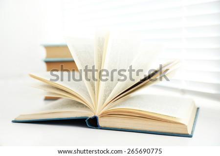 Books on white windowsill, close up - stock photo