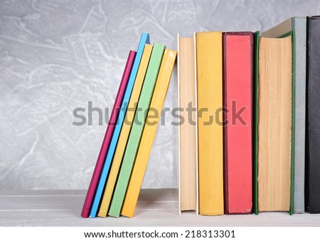 Books on wooden table on light background
