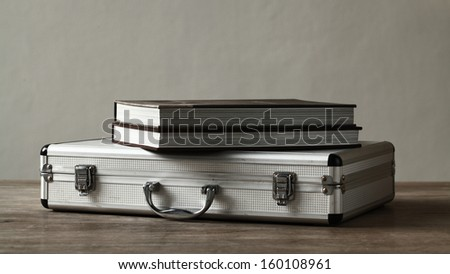Books over aluminum suitcase on wooden table - stock photo