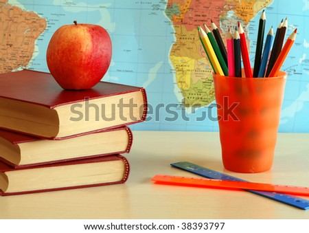 books, pencils, apple and world card