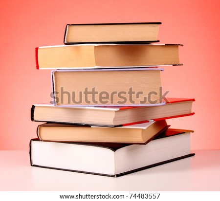 Books pile on the table and red background