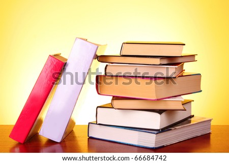 Books pile on the table and yellow background