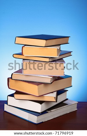 Books pile on the table and yellow background - stock photo