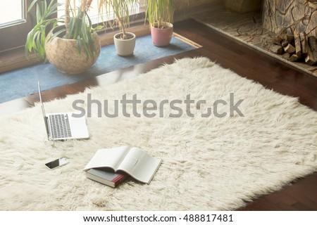 white carpet floor. books, smartphone and laptop lying on white carpet in modern luxury living room interior, floor n