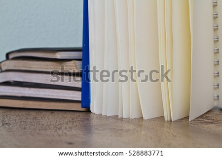 Books stack and fanned pages on wooden deck background