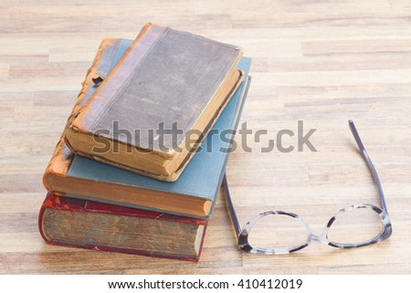 Books stack and glasses on wooden table desktop - stock photo