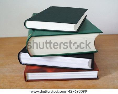 Books. Stack of multi colored books on wooden table. Books and education concept. - stock photo