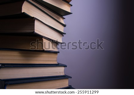 Books stacking. Back to school. Purple background. - stock photo