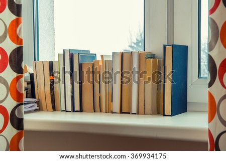 books stand on a windowsill near the window - stock photo
