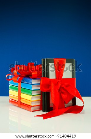Books tied up with ribbon and electronic book reader against blue background - stock photo
