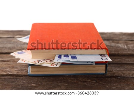 Books with nested euro banknotes on white background. Stash of money - stock photo