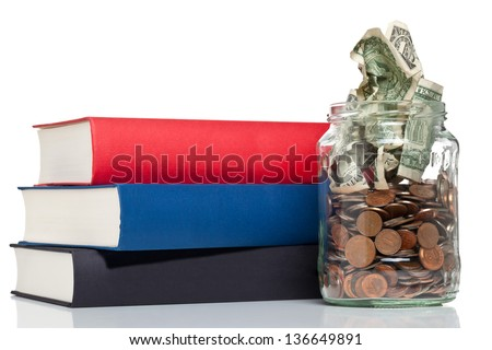Books with penny jar filled with coins and banknotes - tuition or education financing concept - stock photo