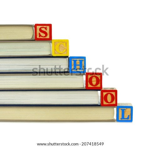 Books with toy wooden blocks spelling SCHOOL over white - stock photo