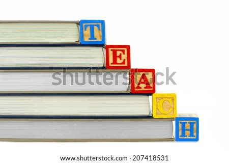 Books with toy wooden blocks spelling TEACH over white - stock photo
