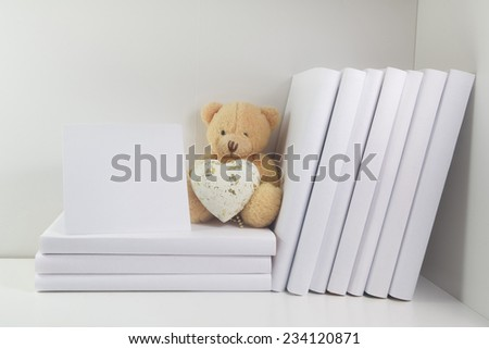 Bookshelf and books in white color, teddy bear with heart - stock photo
