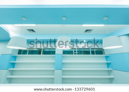 bookshelf and white ceiling lamp in empty modern library - stock photo