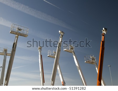 Boom lifts against the sky - stock photo