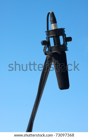 Boom mike with foam windscreen using an xlr plug against a clear blue sky background. - stock photo