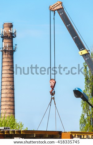 boom of the crane lowers the load. Behind the high brick chimney boiler  - stock photo