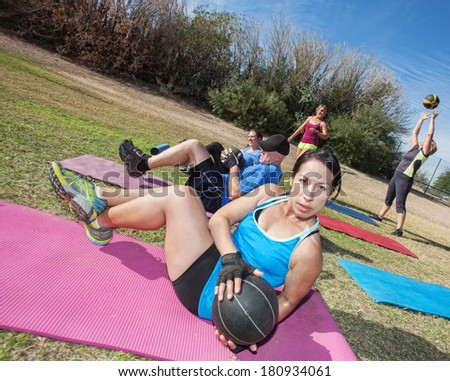 Boot camp fitness class working out on mats outdoors - stock photo