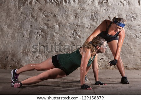 Boot camp training instructor helping lady with push-ups - stock photo