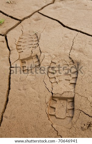 Boot footprints in dry cracked earth - stock photo