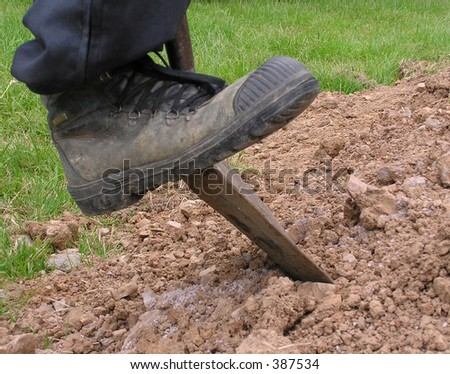 Boot pushing spade into earth - stock photo