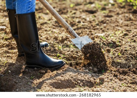 Boot shoveling ground in the garden - stock photo